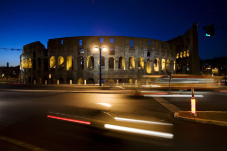 The Colosseum at night with traffic lights . Rome, Italy